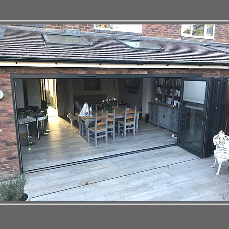 A 5 pane Smart Aluminium bi-folding door in anthracite grey finish with integral blinds installed in solihull, www.solihullwindows.co.uk