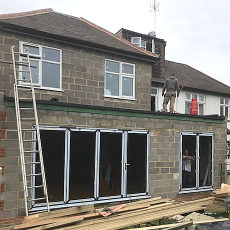 a 4 pane and 2 pane smarts aluminium bi-folding door being installed in North Wembley, London by Solihull WDC (www.solihullwindows.co.uk)