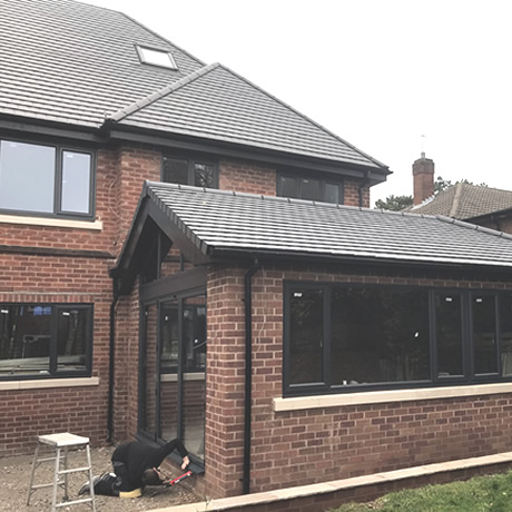 A Smart Aluminium bi-folding door and windows finished in anthracite grey finish installed in St. Bearnards Road, Solihull