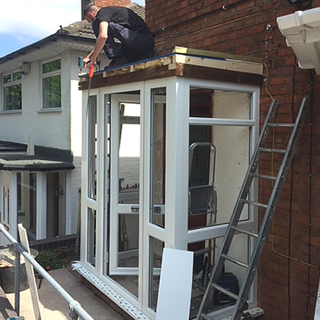 A newbuild entrance porch under construction with white profile and flat roof installed in Solihull by Solihull WDC